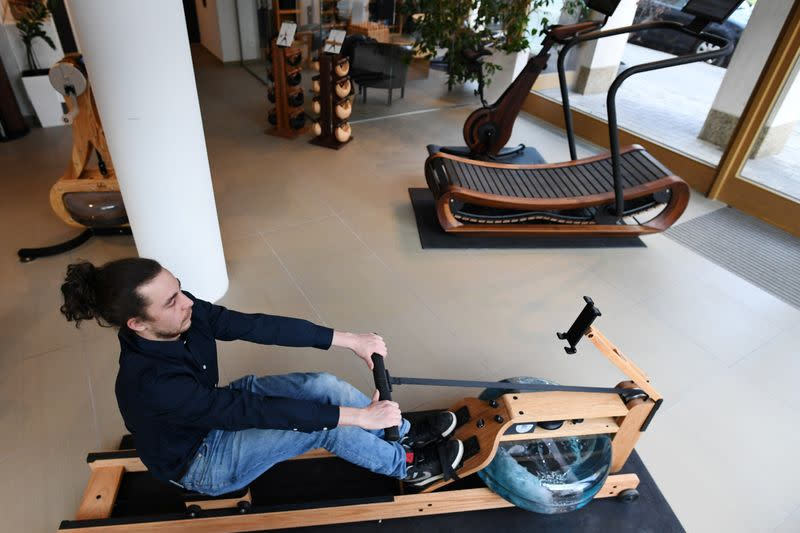A man tries out a rowing machine in a showroom of U.S. gym equipment manufacturer WaterRower in Munich