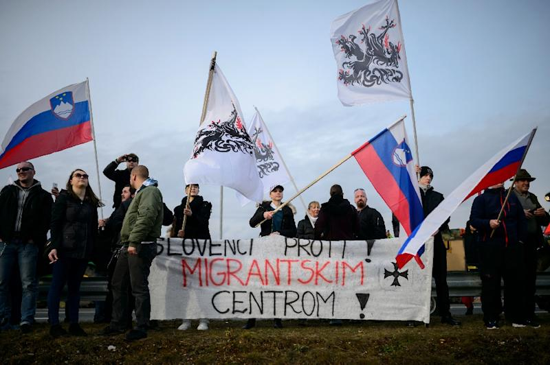 "People wave Slovenian flags and hold a banner reading ""Slovenians against the migrant center"" during a protest against the possible opening of a center for migrants in the vicinity of the town of Sencur, north of Ljubljana, on February 20, 2016"