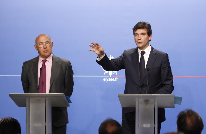 Arnaud Montebourg, Minister for Industrial Recovery, right, and Employment Minister Michel Sapin gesture during a press conference in Paris, Wednesday, July 25, 2012. The French government has unveiled a plan to prop up the struggling auto industry, which is threatening to eliminate thousands of jobs. Wednesday's plan focuses on making France a center for production of environmentally friendly cars. (AP Photo/Remy de la Mauviniere, Pool)