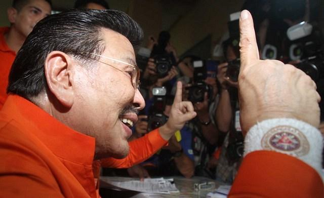 Former President Joseph Estrada flashes the United Nationalist Alliance sign as he files his certificate of candidacy for Manila mayor at the Commission on Elections office in Arroceros Street Oct. 2. (Mike Alquinto, NPPA Images)