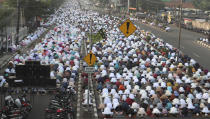 Muslim perform Eid al-Fitr prayer marking the end of the holy fasting month of Ramadan on a street in in Bekasi , West Java, Indonesia, Thursday, May 13, 2021. (AP Photo/Achmad Ibrahim)