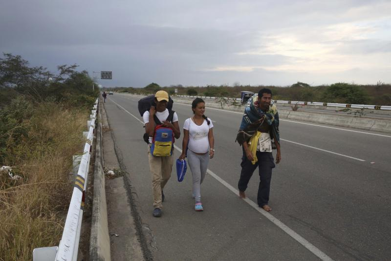 Venezuelan migrants walk on the Pan-American Highway, after crossing the Ecuadorian border into Tumbes, Peru, Friday, June, 14, 2019. Those fleeing the troubled South American nation filed more than one in five of all asylum requests made in 2018. That's higher than requests made by people escaping Afghanistan and Syria. (AP Photo/Martin Mejia)