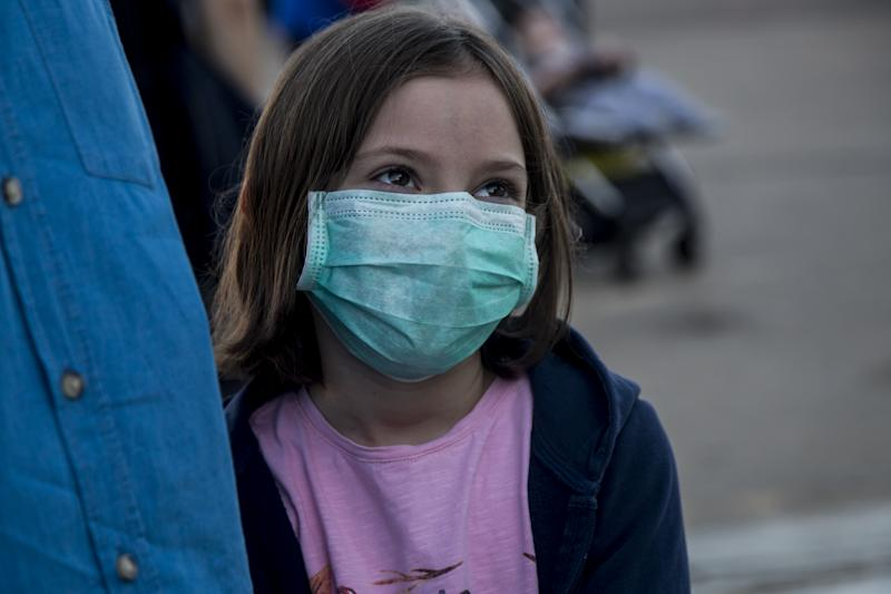 KHARTOUM, SUDAN - APRIL 22: A Turkish girl wears a face mask as a preventive measure against the coronavirus (COVID-19) pandemic as Turkish citizens arrive at Khartoum International Airport ahead of a flight to Turkey as part of the evacuation process due to the pandemic in Khartoum, Sudan on April 22, 2020. Turkey evacuates 363 citizens from Sudan upon their application to the embassy amid the novel coronavirus pandemic. (Photo by Mahmoud Hjaj/Anadolu Agency via Getty Images)