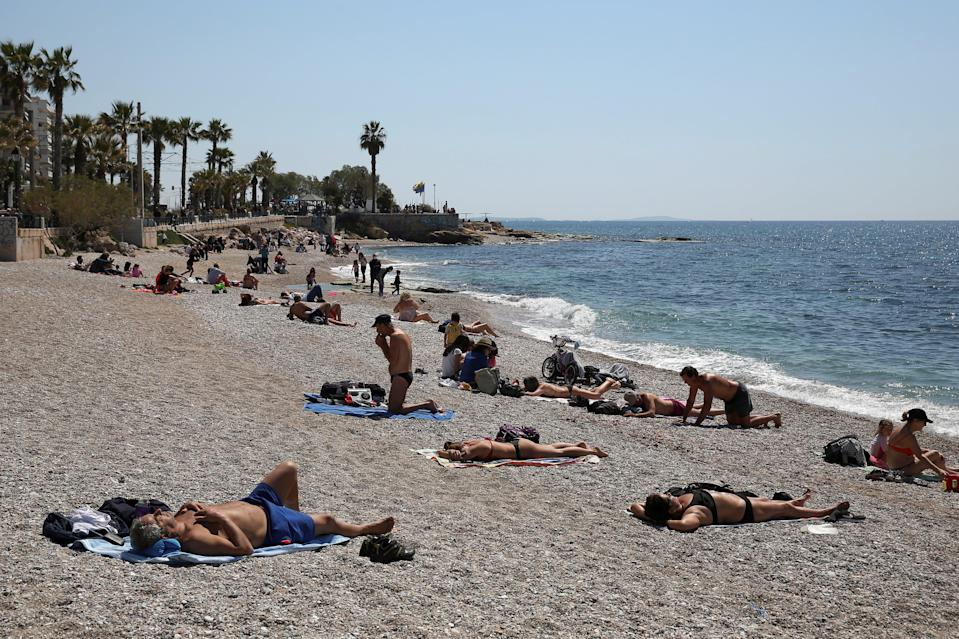 <p>People enjoying the beach in a suburb of Athens, Greece</p> (REUTERS)
