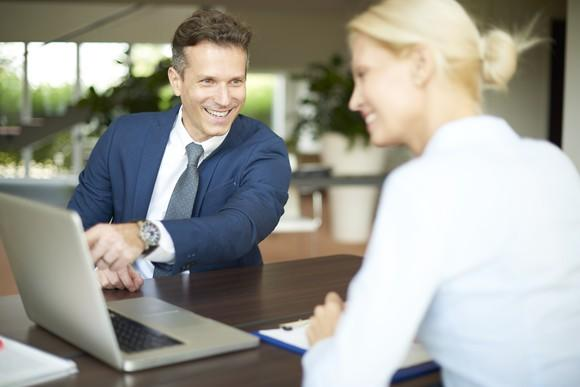 Man and woman in business attire happily looking at computer screen