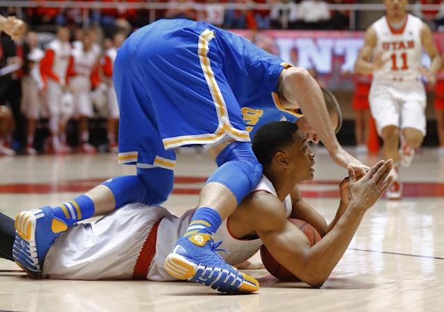 UCLA's Travis Wear, top, fights for a loose ball with Utah's Princeton Onwas, who calls for a timeout during the first half of an NCAA college basketball game in Salt Lake City, Saturday, Jan. 18, 2014. (AP Photo/George Frey)