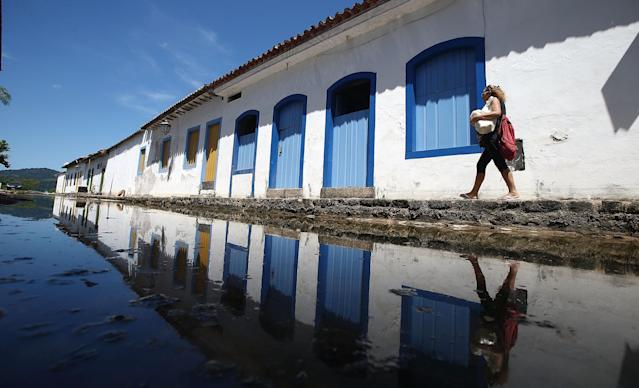 PARATY, BRAZIL - MARCH 14: A woman walks past the flood waters in the historic center of town on March 14, 2014 in Paraty, Brazil. Parts of the historic center flood monthly around the time of the full moon when tides rise. Paraty was built as a Portuguese colonial town shortly after Portugal colonized Brazil in 1500. Paraty flourished during the 18th Century as the main port to ship Brazilian gold to Portugal. The town fell by the wayside and was only re-discovered by travelers in the mid 20th Century, its historic center is well preserved and the cobblestone streets remain closed to automobiles. (Photo by Mario Tama/Getty Images)