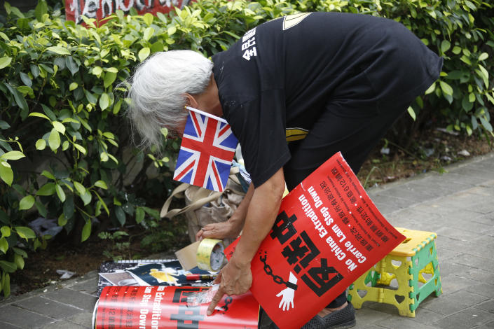 """In this Thursday July 4, 2019, photo, Alexandra Wong, 63, a protester who's often seen raising the Union Jack at demonstrations and carried one into the legislative building on Monday night holds a poster that reads """"Against Tradition to China"""" and a flag outside the Central Government Office in Hong Kong. (AP Photo/Andy Wong)"""