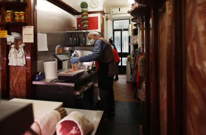 In this photo taken on Thursday, March 12, 2020, a shopkeeper works in a deli meat and cold cuts shop in Codogno, Italy. The northern Italian town that recorded Italy's first coronavirus infection has offered a virtuous example to fellow Italians, now facing an unprecedented nationwide lockdown, that by staying home, trends can reverse. Infections of the new virus have not stopped in Codogno, which still has registered the most of any of the 10 Lombardy towns Italy's original red zone, but they have slowed. For most people, the new coronavirus causes only mild or moderate symptoms. For some it can cause more severe illness. (AP Photo/Antonio Calanni)