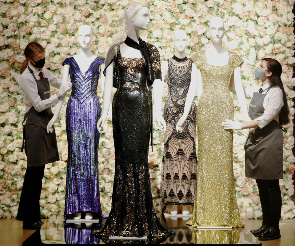 Gallery assistants handle a selection of dresses, including a gold sequined gown, right, worn by Penelope Cruz, amongst other items on display at Christie's, from the archive of fashion designer L'Wren Scott before it is offered at auction, in London, Thursday June 10, 2021. (Jonathan Brady/PA via AP)