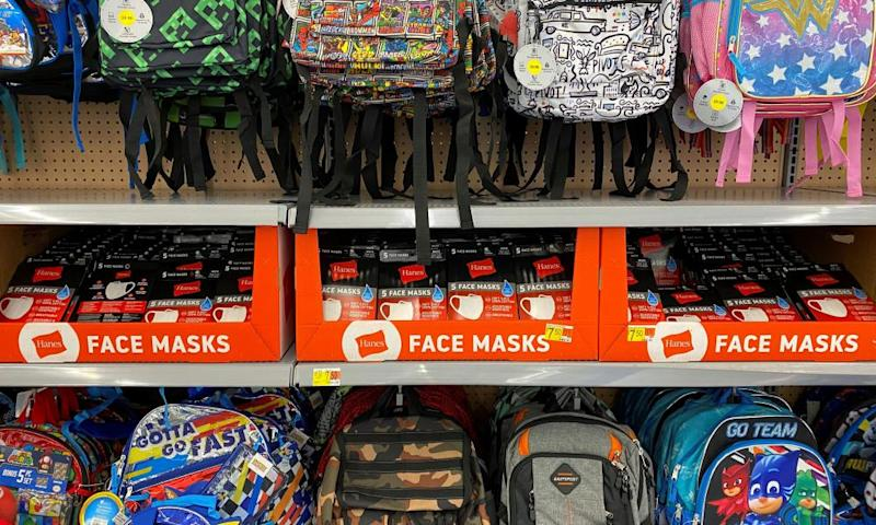 Face masks are shown for sale with backpacks and back to school supplies at a Walmart store in Encinitas, California.