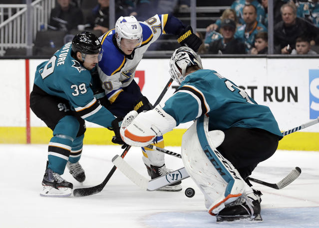 St. Louis Blues' Oskar Sundqvist (70) takes a shot against San Jose Sharks goalie Martin Jones, right, during the third period of an NHL hockey game Saturday, March 9, 2019, in San Jose, Calif. Also defending is Sharks' Logan Couture (39). (AP Photo/Ben Margot)