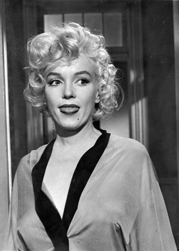 Marilyn Monroe, circa 1955, sticks her tongue out during filming of a movie.