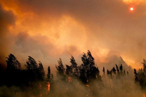 The setting sun is partially obscured by smoke from an out of control wildfire on the Parks Highway near Willow, Alaska, on June 14, 2015. Zombie fires, also known as overwintering fires or holdover fires, are more common after hot, dry fire seasons with large fires.
