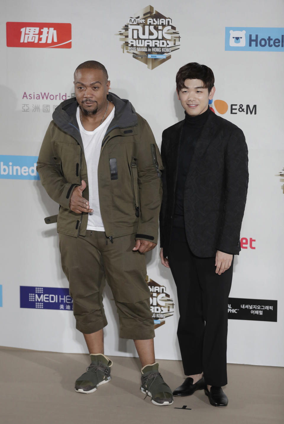 """FILE - In this Dec. 2, 2016 file photo, American musician Timothy Zachery """"Tim"""" Mosley, known professionally as Timbaland, left, and South Korean-American singer-songwriter Eric Nam, pose for the photographers on the red carpet of the 2016 Mnet Asian Music Awards (MAMA) in Hong Kong. Korean American K-pop singers, including Nam, are sharing their experiences with stress in a series of podcasts addressing mental health issues to raise awareness beyond the K-pop community. (AP Photo/Kin Cheung, File)"""