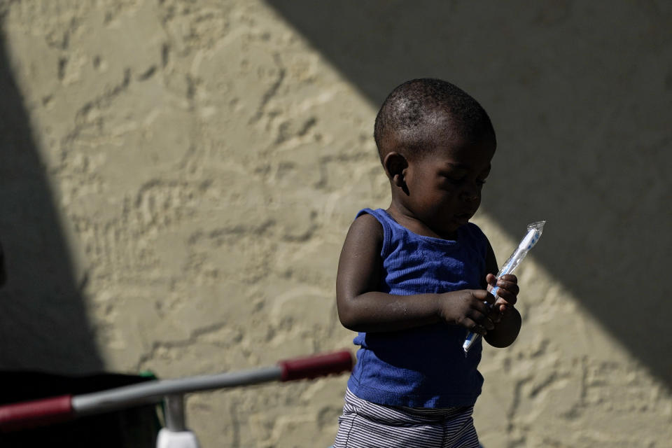 A Haitian migrant boy holds a toothbrush as he waits with his father to board a bus to Houston provided by a humanitarian group after they were released from U.S. Customs and Border Protection custody, Friday, Sept. 24, 2021, in Del Rio, Texas. (AP Photo/Julio Cortez)