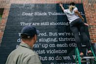 Artist Tatyana Fazlalizadeh hangs up a poster in the Greenwood district of Tulsa on May 28, 2021 in Tulsa, Oklahoma, ahead of the commemoration for the 100th anniversary of the Tulsa Race Massacre