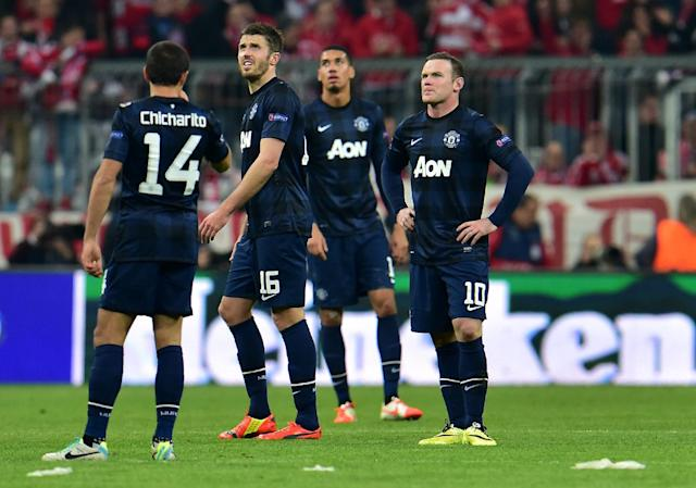 Manchester United's Wayne Rooney, right, looks on after Munich scored the third goal during the Champions League quarterfinal second leg soccer match between Bayern Munich and Manchester United in the Allianz Arena in Munich, Germany, Wednesday, April 9, 2014. (AP Photo/Kerstin Joensson)