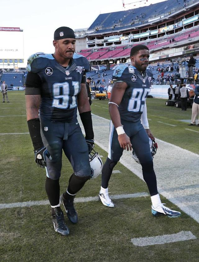 Tennessee Titans defensive end Derrick Morgan (91) and wide receiver Nate Washington (85) leave the field after the Jacksonville Jaguars defeated thems 29-27 in an NFL football game on Sunday, Nov. 10, 2013, in Nashville, Tenn. (AP Photo/Wade Payne)