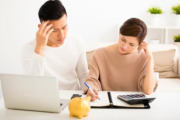 Couple adding up their finances with a calculator