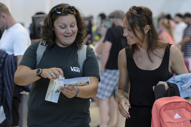 Tourists smile after checking in an alternate flight, at the Cancun airport in Mexico, Monday, Sept. 23, 2019. British tour company Thomas Cook collapsed early Monday after failing to secure emergency funding, leaving tens of thousands of vacationers stranded abroad. (AP Photo/Victor Ruiz)