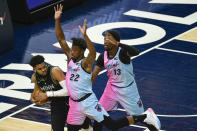 Minnesota Timberwolves center Karl-Anthony Towns, left, is defended by Miami Heat forward Jimmy Butler(22) and center Bam Adebayo(13) during the first half of an NBA basketball game Friday, April 16, 2021, in Minneapolis. (AP Photo/Craig Lassig)