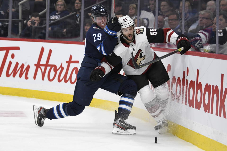 Winnipeg Jets' Patrik Laine (29) checks Arizona Coyotes' Jason Demers (55) during the second period of an NHL hockey game Tuesday, Oct. 15, 2019, in Winnipeg, Manitoba. (Fred Greenslade/The Canadian Press via AP)