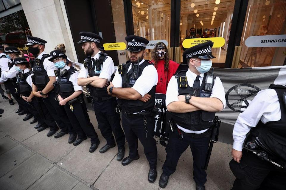 Police officers stand next to climate activists who glued themselves to the wall of the Selfridges (REUTERS)