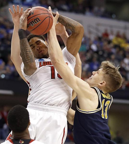 Louisville's Ray Spalding, left, and Michigan's Moritz Wagner reach for a rebound during the first half of a second-round game in the men's NCAA college basketball tournament Sunday, March 19, 2017, in Indianapolis. (AP Photo/Jeff Roberson)