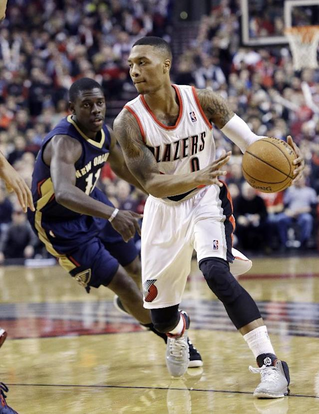 Portland Trail Blazers guard Damian Lillard, right, drives past New Orleans Pelicans guard Jrue Holiday during the first half of an NBA basketball game in Portland, Ore., Saturday, Dec. 21, 2013. (AP Photo/Don Ryan)
