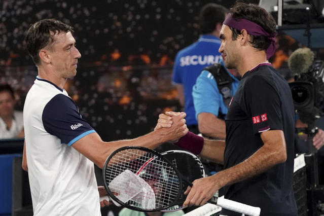FILE - In this Jan. 25, 2020, file photo, Australia's John Millman, left, shakes hands with Switzerland's Roger Federer following their match at the Australian Open tennis championship in Melbourne, Australia. Just four matches after his five-setter against Federer on one of the biggest stages in tennis, Millman was having to scramble to find a practice court. (AP Photo/Lee Jin-man, File)