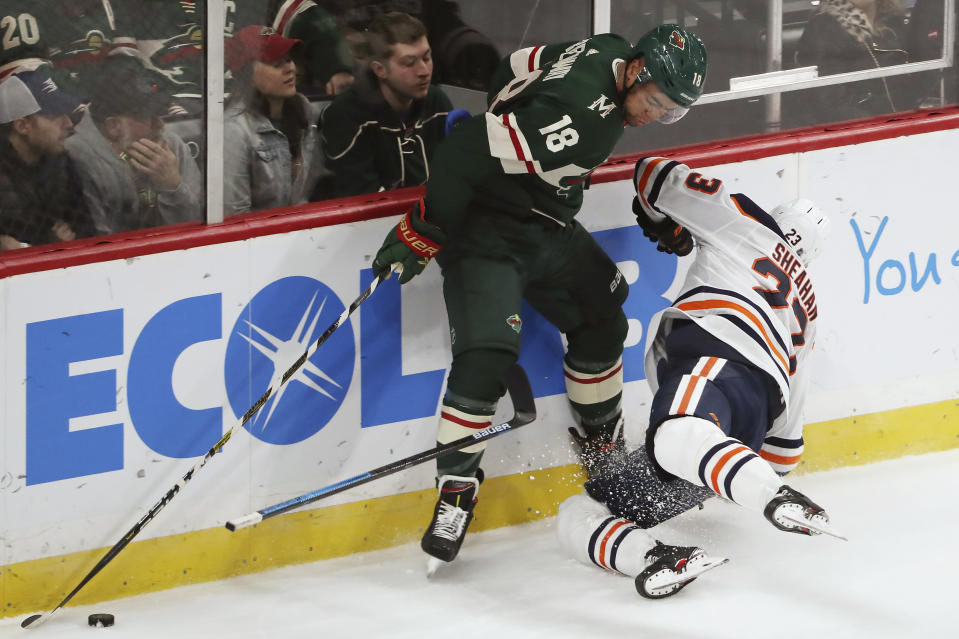 Minnesota Wild's Jordan Greenway (18) crashes with Edmonton Oilers' Riley Sheahan (23) while trying to get the puck during the first period of an NHL hockey game Tuesday. Oct. 22, 2019, in St. Paul, Minn. (AP Photo/Stacy Bengs)