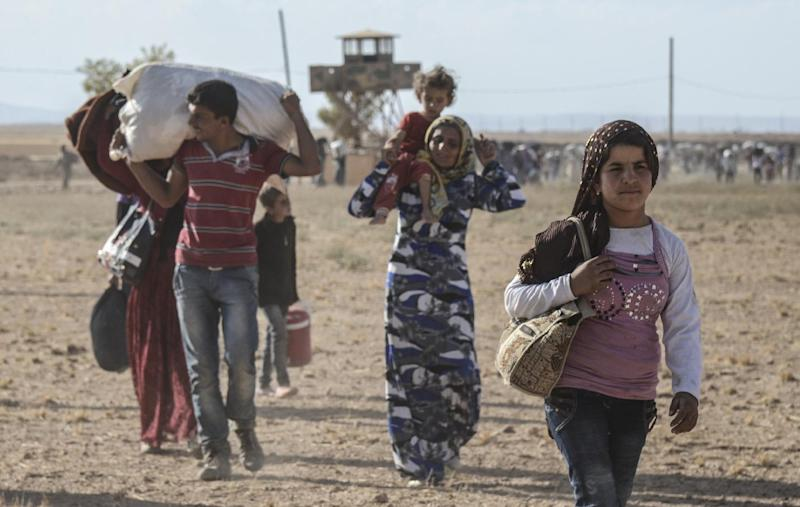 Syrian Kurds cross the border between Syria and Turkey in Sanliurfa province, on September 19, 2014