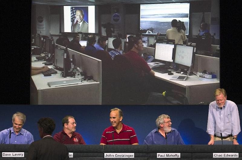 NASA scientists smile after NASA's Administrator Charles Bolden, seen on video projection on top left, debuted the first recorded human voice that traveled from Earth to another planet and back, as Bolden radioed the rover on Mars and back to NASA's Deep Space Network (DSN) on Earth, during a briefing at NASA's Jet Propulsion Laboratory in Pasadena, Calif., Monday, Aug. 27, 2012. From left: Mike Malin, imaging scientist for the Mars Science Laboratory, John Grotzinger, MSL project scientist, California Institute of Technology, Paul Mahaffy, NASA Goddard Space Flight Center, and Dr. Chad Edwards, Chief Telecommunications Engineer for the Mars Exploration Program at JPL. (AP Photo/Damian Dovarganes)