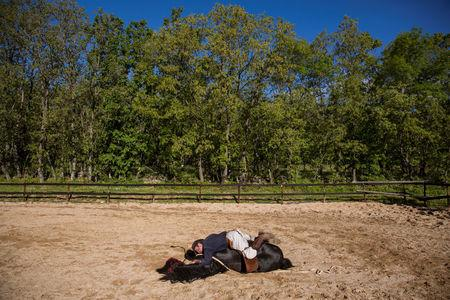 Fernando Noailles, emotional therapist, lays on top of his horse named Madrid in Guadalix de la Sierra, outside Madrid, Spain, May 31, 2016. Noailles uses his animals to help people suffering from stress and anxiety. REUTERS/Juan Medina