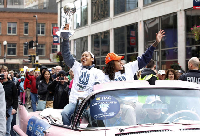 Minnesota Lynx forward Maya Moore, left, and guard Seimone Augustus, right, celebrate during the parade for their WNBA basketball championship title, Monday, Oct. 14, 2013, in Minneapolis. (AP Photo/Stacy Bengs)