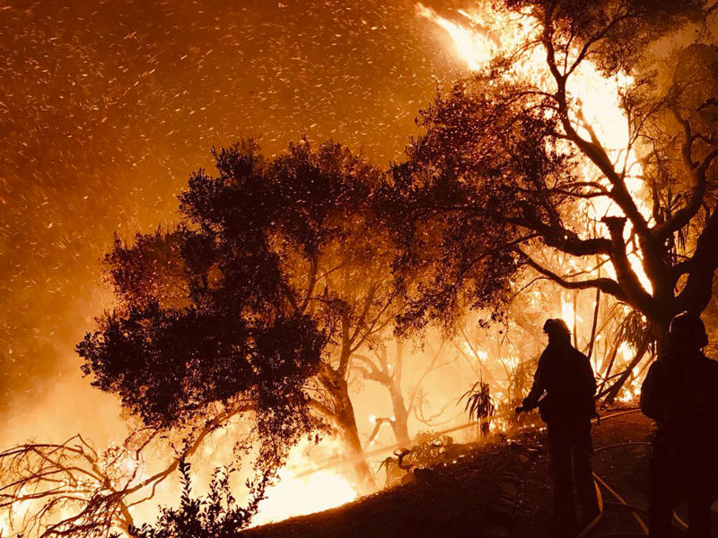 In this Sunday, Dec. 10, 2017 photo released by Santa Barbara County Fire Department firefighters knock down flames as they advance on homes atop Shepherd Mesa Road in Carpinteria, Calif. A flare-up on the western edge of Southern California's largest and most destructive wildfire sent residents fleeing Sunday, as wind-fanned flames churned through canyons and down hillsides toward coastal towns. Crews with help from water-dropping aircraft saved several homes as unpredictable gusts sent the blaze churning deeper into foothill areas northwest of Los Angeles that haven't burned in decades. New evacuations were ordered in Carpinteria, a seaside city in Santa Barbara County that has been under fire threat for days. (Mike Eliason/Santa Barbara County Fire Department via AP)