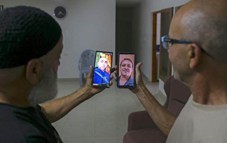 Malek Hassuna, left, holds up his phone with a picture of his late son Mussa, and Effi Yehoshua shows a photo of his late brother Yigal (AFP/AHMAD GHARABLI)