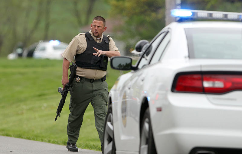 Law enforcement works the scene Friday, May 10, 2013 after two escaped convicts from a northeast Kansas prison holed up in a house in Edgerton, Mo. Allen M. Hurst, 31, and Scott A. Gilbert, 49, surrendered willingly after a seven hour standoff. The whereabouts of 57-year-old Randy A. Ridens Sr., who escaped with the other two men, are not known. (AP Photo/St. Joseph News-Press, Jessica Stewart)