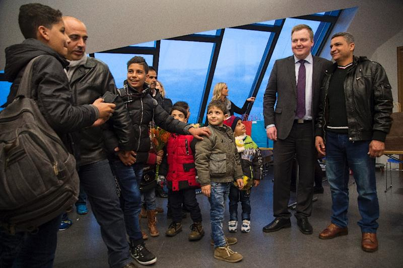 Iceland's Prime Minister Sigmundur David Gunnlaugsson (2R) poses with a man of the first group of Syrian refugees on January 19, 2016 upon their arrival at Keflavik airport