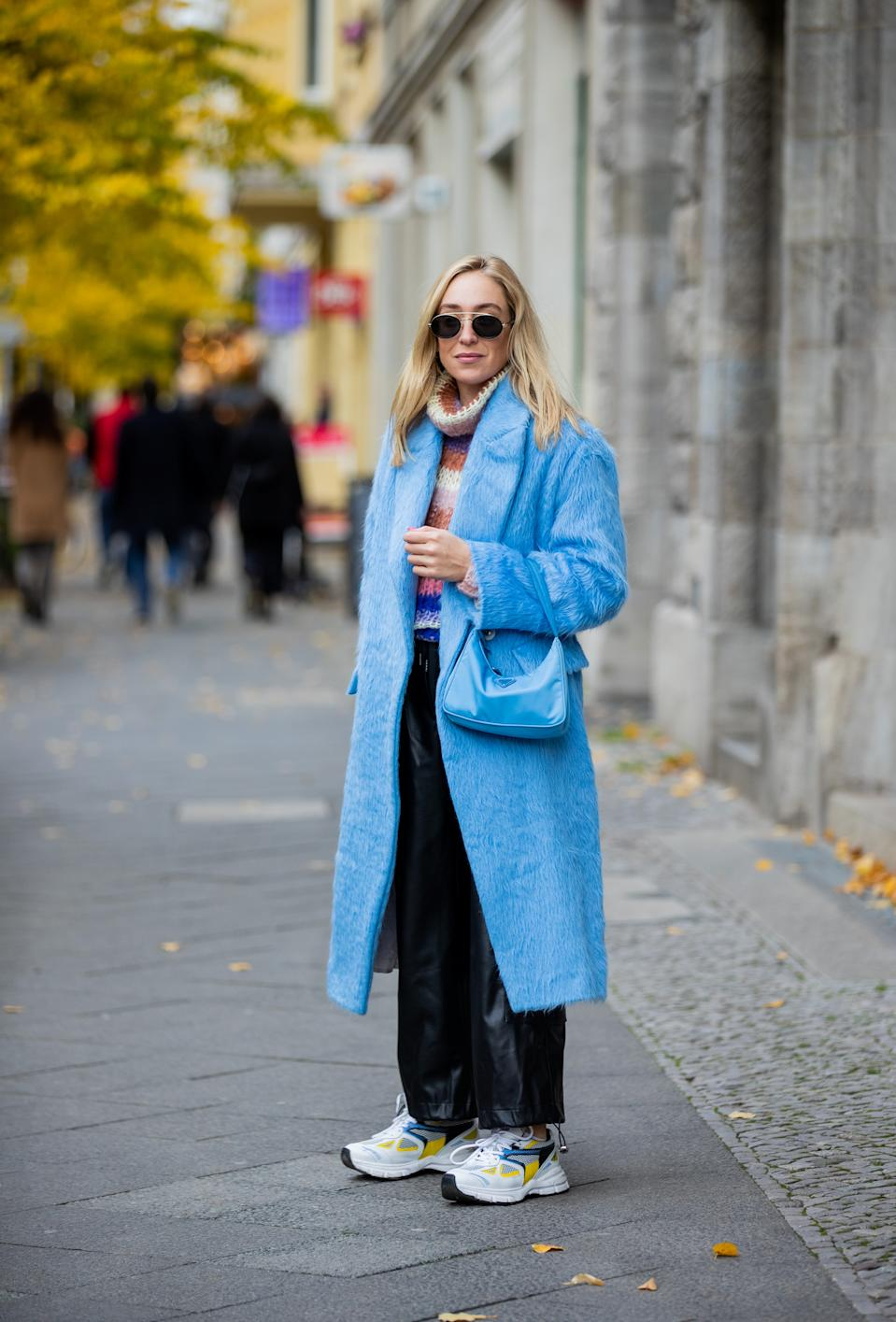 BERLIN, GERMANY - OCTOBER 28: Sonia Lyson is seen wearing blue coat Dorothee Schumacher, blue Prada bag, turtleneck knit Maiami Berlin, wide leg pants The Franke Shop, Axel Arigato  sneaker, sunglasses Jimmy Choo on October 28, 2020 in Berlin, Germany. (Photo by Christian Vierig/Getty Images)