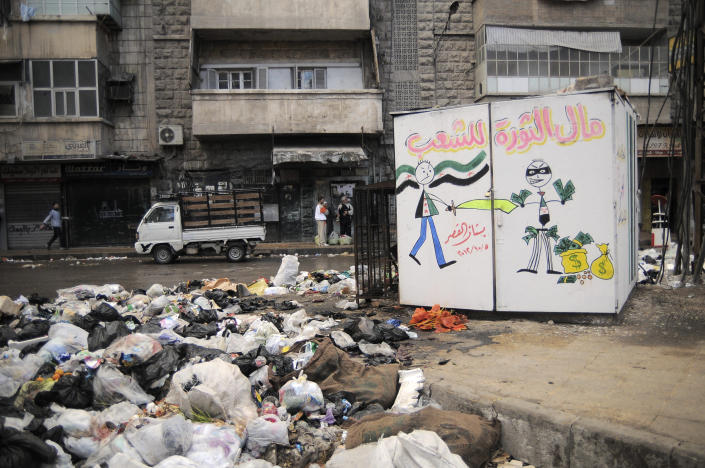 """In this Saturday, Nov. 10, 2012 photo, garbage is plied up in the Al-Buhouth area of Aleppo, Syria. The Arabic writing on the kiosk at right reads, """"the money of the revolution is for the people.""""(AP Photo/Mónica G. Prieto)"""
