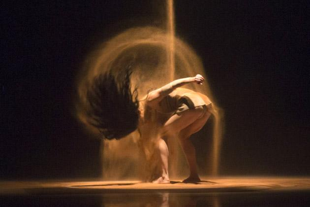 A dancer preforms with sand during Gideon Oberson's show at the Tel Aviv fashion week in the Mediterranean coastal city of Tel Aviv, on December 17, 2012. AFP PHOTO / JACK GUEZ