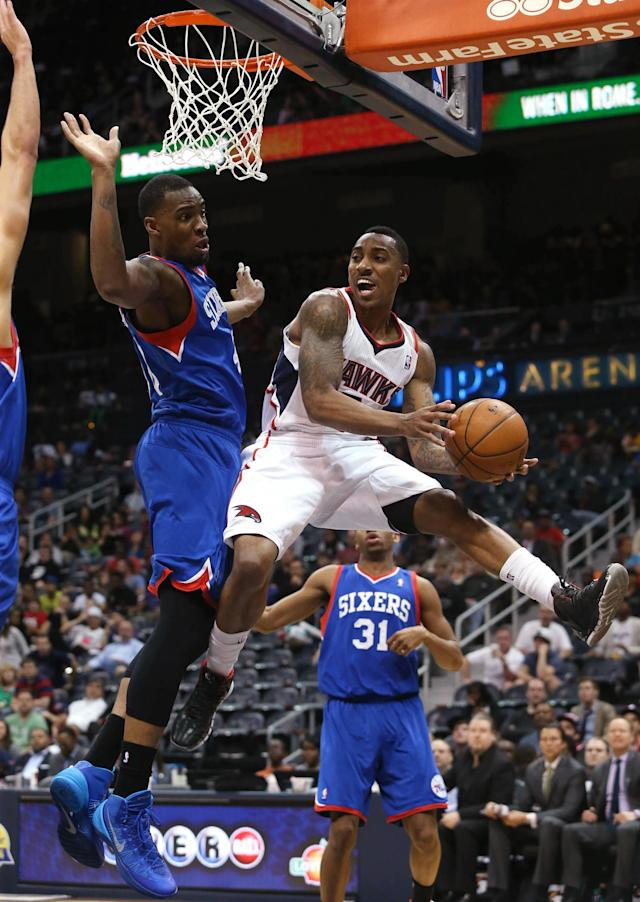 Atlanta Hawks guard Jeff Teague, right, looks to pass under the defense of Philadelphia 76ers forward Jarvis Varnado in the first half of an NBA basketball game Monday, March 31, 2014, in Atlanta. (AP Photo/Jason Getz)