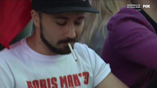 What's going on with guy using flame wallet to light his cigarette at the World Cup? (Photo via Twitter)