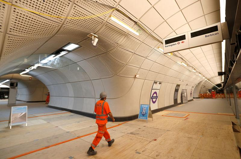 A Crossrail worker walks in the new Farringdon underground station of the Elizabeth line which opens in December 2018, in London