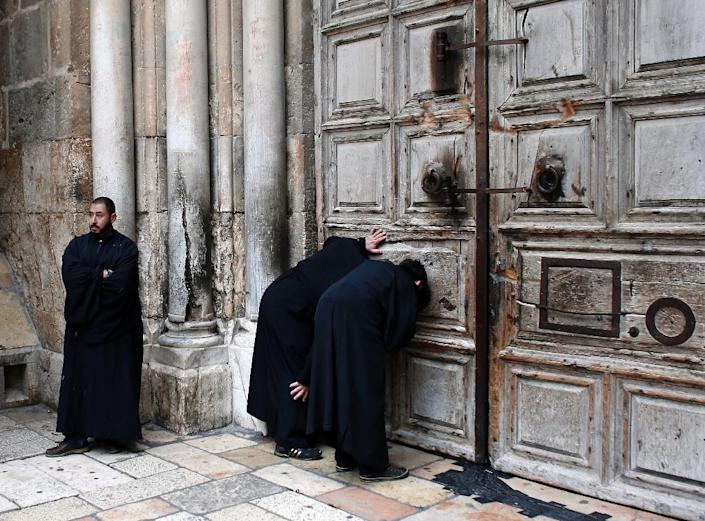 Christian Orthodox priests look through a hole in the main door of the Church of the Holy Sepulchre, before the Holy fire ceremony around Jesus' tomb, in Jerusalem's Old City during the Orthodox Easter ceremony of the 'Holy Fire' on April 11, 2015 (AFP Photo/Thomas Coex)
