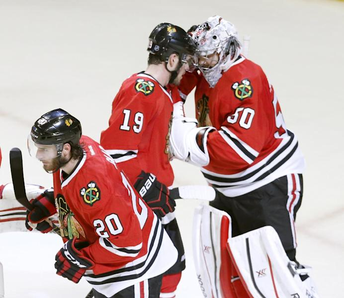 Chicago Blackhawks goalie Corey Crawford, right, celebrates the Blackhawks' 3-1 win over the Los Angeles Kings with Jonathan Toews (19) and Brandon Saad (20) after Game 1 of the Western Conference finals in the NHL hockey Stanley Cup playoffs in Chicago on Sunday, May 18, 2014. The Blackhawks won 3-1. (AP Photo/Charles Rex Arbogast)