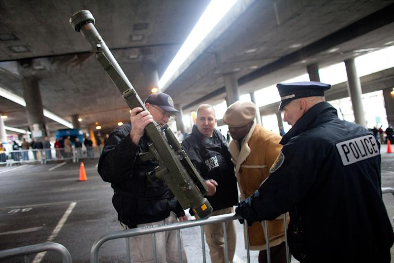 RETRANSMISSION TO CORRECT WEAPON TYPE - Seattle Police Department officers examine an inert surface to air missile launcher brought to the gun buy back program run by the Seattle Police Department on Saturday, January 26, 2013. The city has collected donations totaling nearly $120,000 to pay for a series of gun buyback events. Participants have been asked to unload and secure their weapons in the trunk of their vehicle or in a locked container. (AP Photo/seattlepi.com, Joshua Trujillo) MAGS OUT; NO SALES; SEATTLE TIMES OUT; MANDATORY CREDIT; TV OUT
