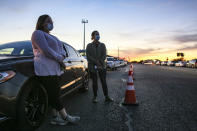 FILE - In this Thursday, Jan. 7, 2021, Cindy Rubiano and Trolena Loya stand outside their car as they wait in line overnight on behalf of their aged parents and in-laws before the COVID-19 vaccine clinic at Casa Del Sol opened on Friday morning in Harlingen, Texas. The U.S. is entering the second month of the largest vaccination effort in history with a massive expansion of the campaign, opening up football stadiums, major league ballparks, fairgrounds and convention centers to inoculate a larger and more diverse pool of people. (Denise Cathey/The Brownsville Herald via AP)